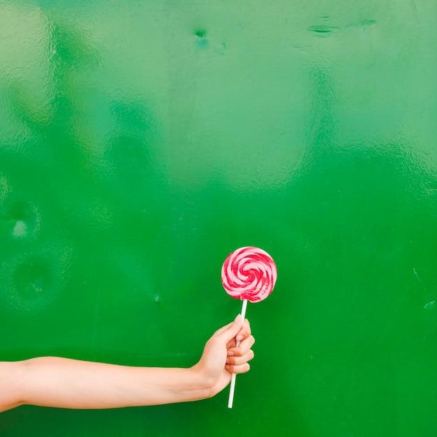 Крупным планом рука женщины, проведение леденец в руке на зеленом фоне Бесплатные Фотографии