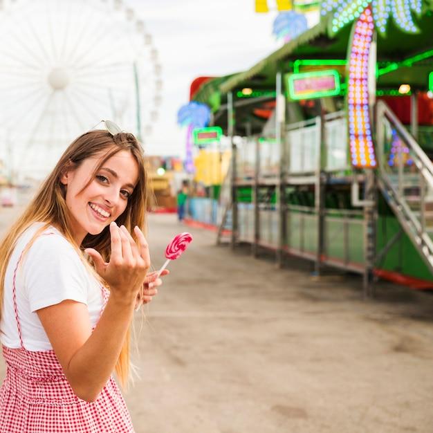 遊園地に来て誰かを招待するロリポップを保持している笑顔の若い女性 無料写真