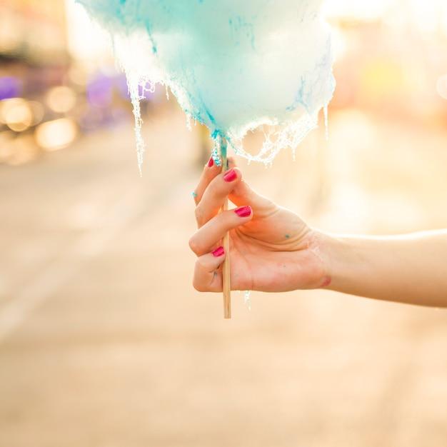 青いキャンディーフロスを保持している女性の手のクローズアップ 無料写真