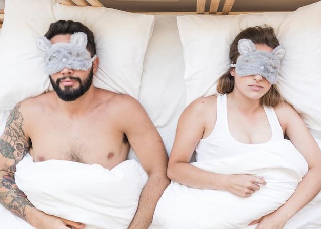 アイマスクでベッドに横たわっている若いカップルの上昇した眺め 無料写真