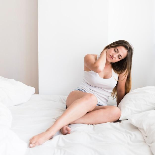 首に痛みを患っているベッドに座っている若い女性 無料写真