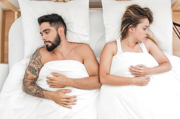 ベッドに横たわっている悲しい夫婦の高い角度の光景 無料写真