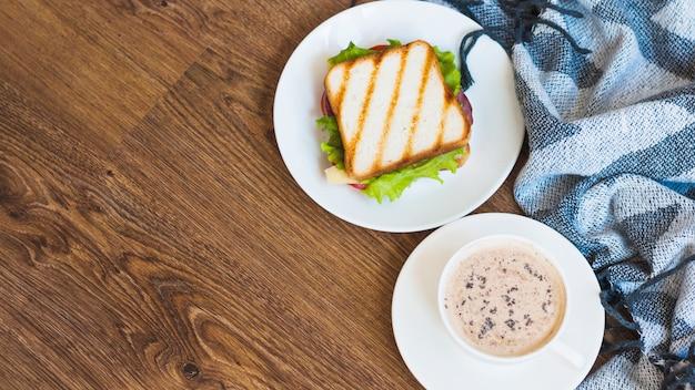 ナプキンと木製のテーブルの上にコーヒーとグリルサンドイッチのカップ 無料写真