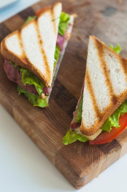 木製のチョッピングボードに焼いたサンドイッチのスライス 無料写真