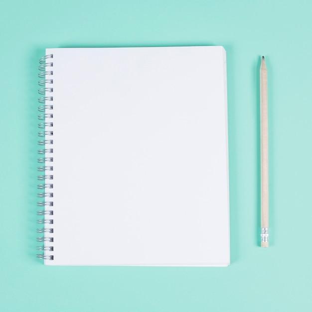 ターコイズ色の背景に鉛筆で空白のスパイラルノート 無料写真