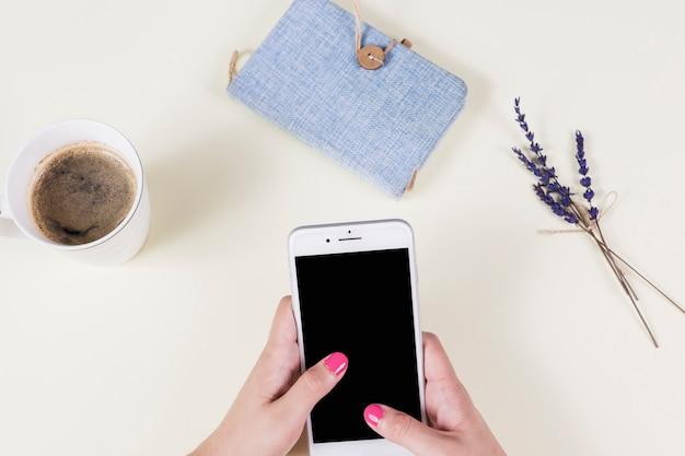コーヒーカップと携帯電話を保持している女性の手;日記、ラベンダー、背景 無料写真