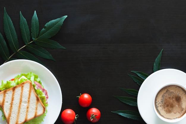 サンドイッチ;トマトと黒の背景に葉のコーヒーカップ 無料写真