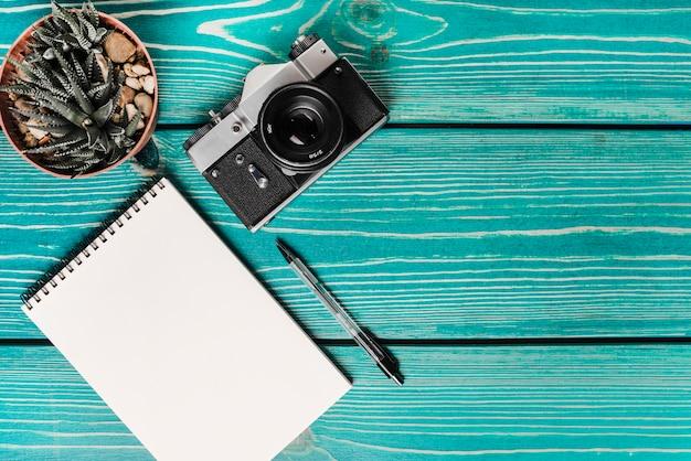 サボテン鉢植え;カメラ;スパイラルノートパッドとペン、ターコイズブルーの木製の板 無料写真