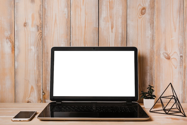 Открытый ноутбук с белым экраном и сотовый телефон на деревянном столе Бесплатные Фотографии