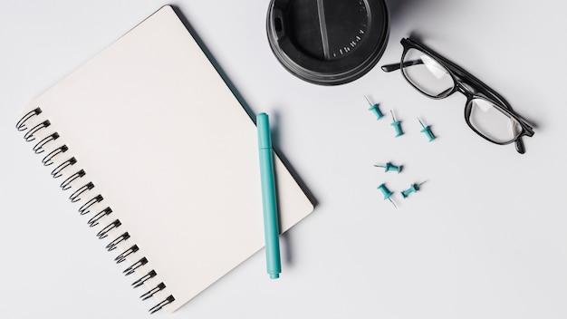 空白のスパイラルメモ帳;ペン;コーヒーカップ;白い背景に眼鏡とプッシュピン 無料写真