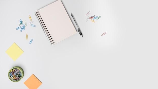 カラフルなクリップ;スパイラルノート;ペン;白い背景に粘着性のノート 無料写真