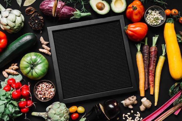 様々な生野菜に囲まれた黒いフレームの高い角度の光景 無料写真