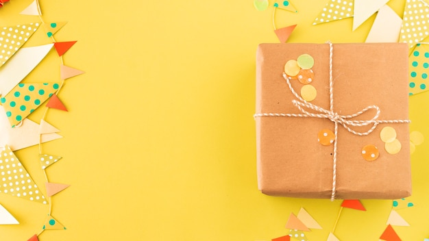 黄色の背景にラッピングされた誕生日プレゼントと房 無料写真