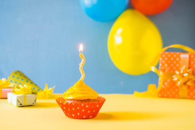 黄色の表面に蝋燭を燃やすとカップケーキ 無料写真