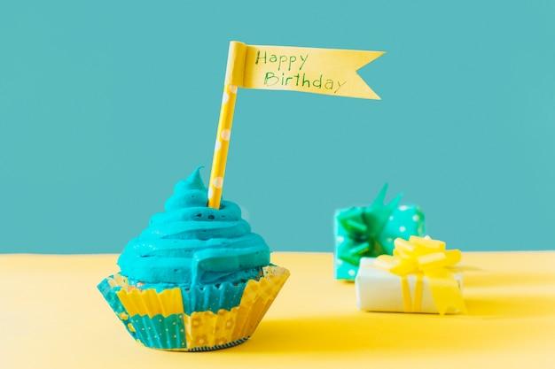黄色の表面に贈り物の近くに幸せな誕生日の旗とおいしいマフィン 無料写真