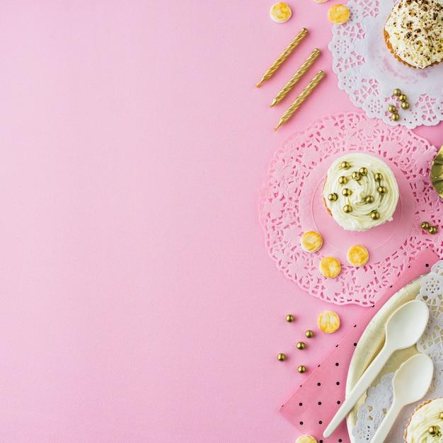 カップケーキの高い角度のビュー;キャンデー、キャンドル、ピンクの背景 無料写真