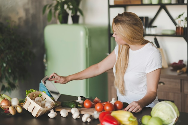 食事を準備しながらデジタルタブレットでブラウジングする若い女性 無料写真