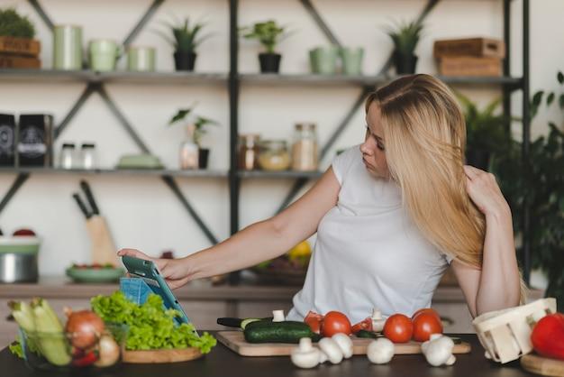 キッチンカウンターで多くの野菜を持つデジタルタブレットをブラウジングする若い女性 無料写真