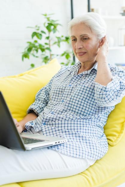Улыбаясь старший женщина, сидя на диване, глядя на ноутбук Бесплатные Фотографии