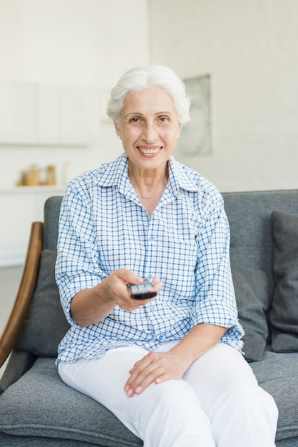 Улыбаясь старший женщина, сидя на диване с помощью дистанционного управления Бесплатные Фотографии
