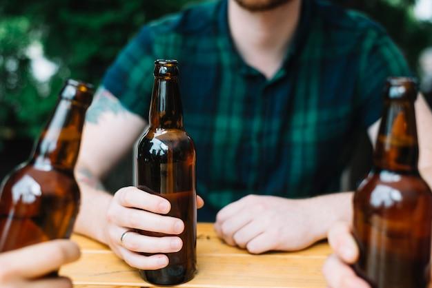 Крупным планом человек, держащий коричневую бутылку пива со своими друзьями Бесплатные Фотографии
