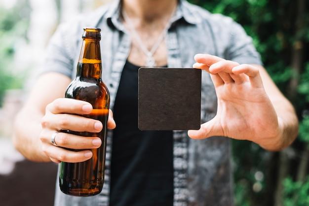 Человек, держащий коричневый бутылка пива и черная пустая карточка в руках Бесплатные Фотографии