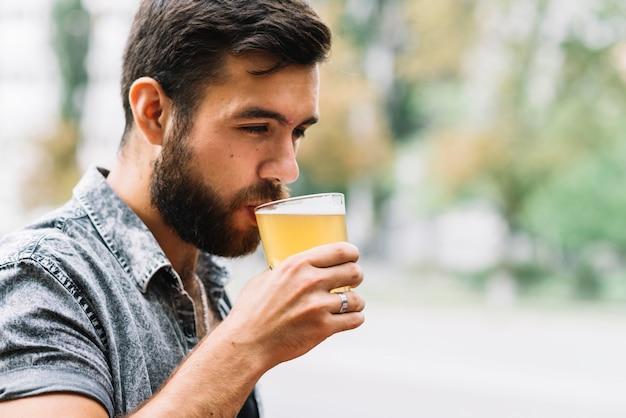 Крупный план человек, пить стакан пива на открытом воздухе Бесплатные Фотографии