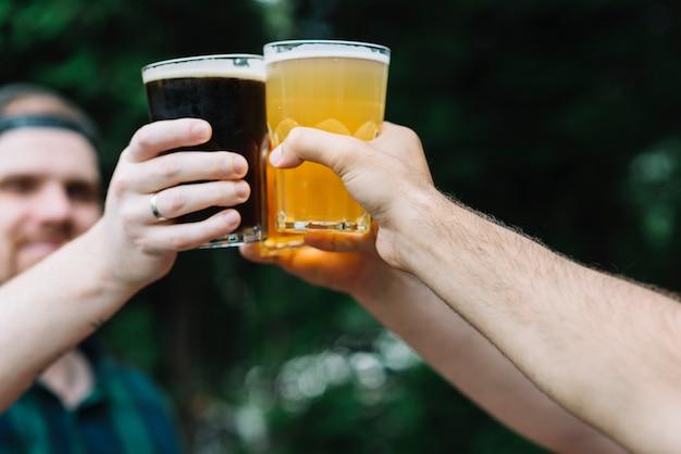 Крупный план руки друга подбадривает стакан алкогольных напитков Бесплатные Фотографии