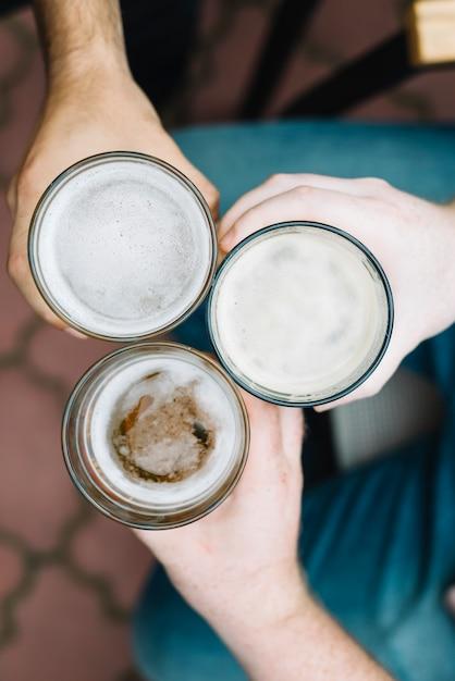 男性の友人のトーストガラスのアルコール飲料の高い角度のビュー 無料写真