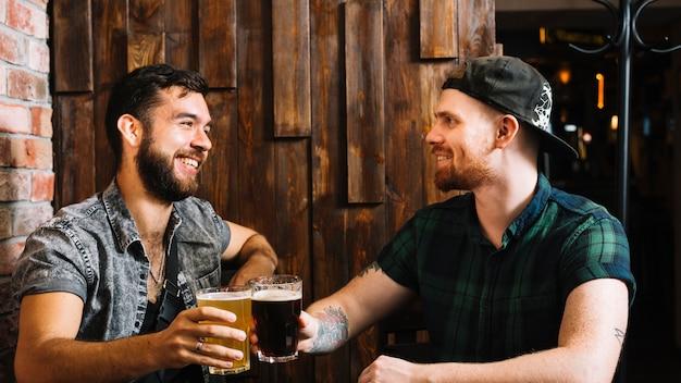 アルコール飲料のガラスを食べる幸せな男性の友人 無料写真