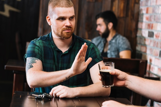 彼の友人が提供するアルコール飲料をバーで拒否している男 無料写真