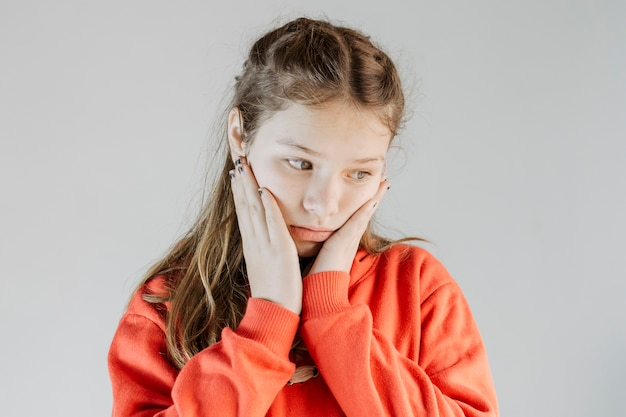 灰色の背景に怒っている女の子のクローズアップ 無料写真