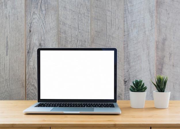 白い空白の画面をテーブルに表示している開いたラップトップの近くにサボテンの白い鉢植えの植物 無料写真