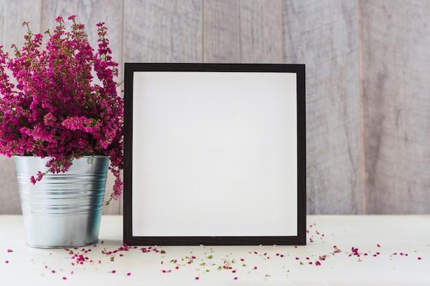 ピンクの花とテーブルの上に白い四角形のフォトフレームのアルミポット 無料写真