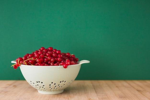 緑色の背景の前にある机の上の小葉に、新鮮な赤いカラントの果実 無料写真