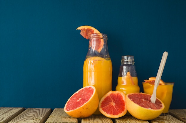 Половина грейпфрута с соком на стол на синем фоне Бесплатные Фотографии