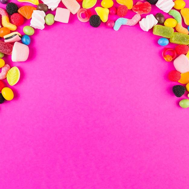 Красочные сладкие конфеты, образующие форму дуги на розовом фоне Бесплатные Фотографии