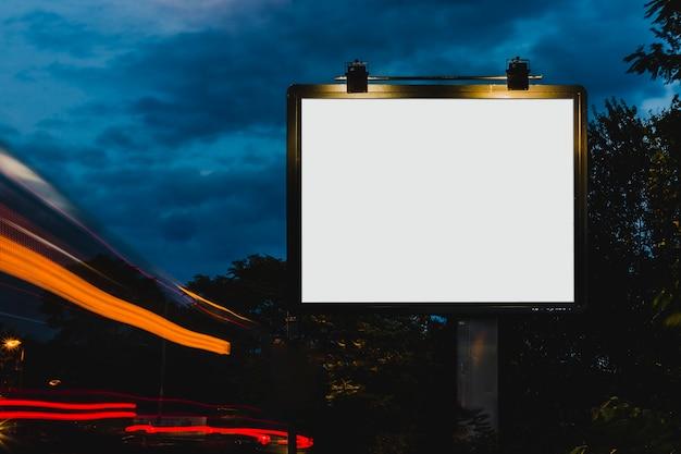 夜の広告のための白いブランクの看板の近くのぼやけた道の光 無料写真