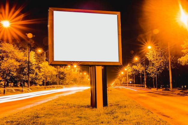 夜のダウンタウン地区にある軽歩道の空白の広告掲示板 無料写真