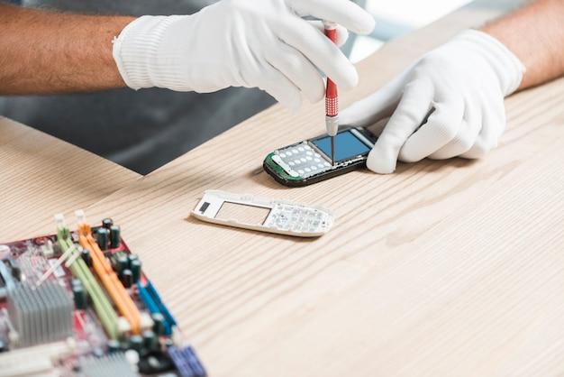 携帯電話を修復する技術者の手のクローズアップ 無料写真