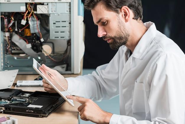 デジタルタブレットを使用している男性の技術者の側面図 無料写真