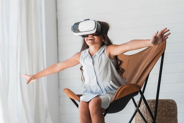 自宅で仮想現実眼鏡を着て椅子に座っている驚くべき女の子 無料写真