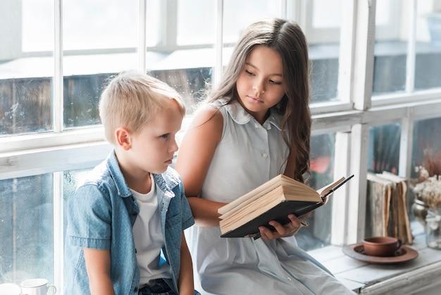 窓の敷居の読書の近くに座っている少年のクローズアップ 無料写真