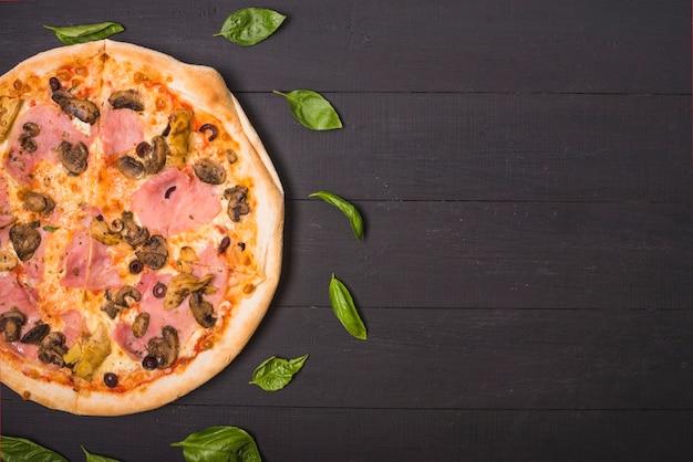 木製の厚板にバジルの葉で飾られた自家製のピザのオーバーヘッドビュー 無料写真
