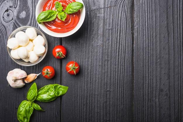 トマトソースとモッツァレラのボウルとバジルとガーリックの木製テーブル 無料写真
