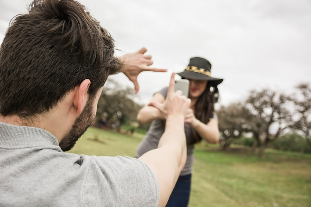 Женщина говорит фото человека, делая ручную рамку в парке Бесплатные Фотографии
