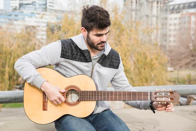 公園に座ってギターを弾くハンサムな若い男 無料写真