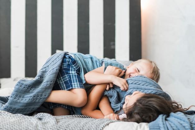 幸せな男の子と女の子がベッドで遊ぶ 無料写真