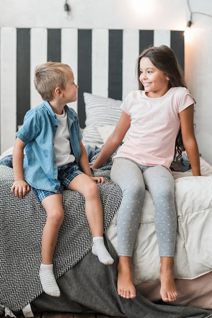 兄弟とお互いを見てベッドに座っている少女 無料写真