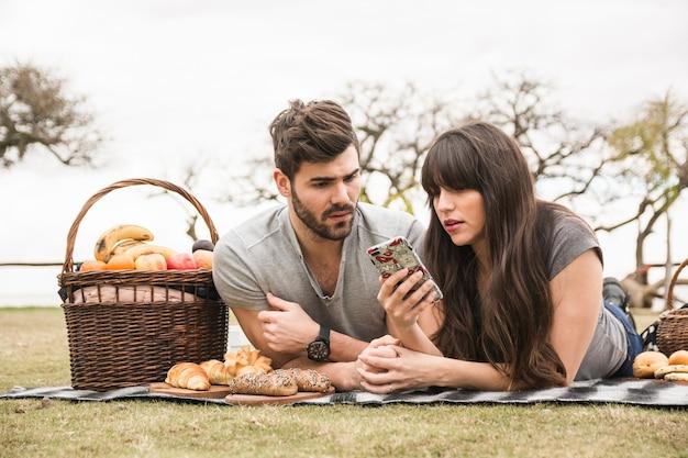 携帯電話を見てピクニックで若いカップル 無料写真